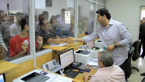 Un funcionario desembolsa el dinero de la ayuda qatarí a los civiles de Gaza en un banco postal local.
