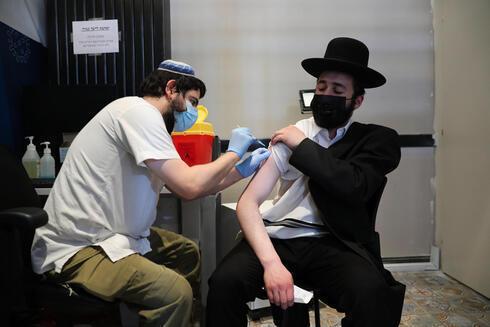 Un hombre haredí recibiendo la tercera inyección en Tel Aviv.