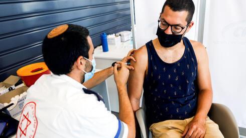 Un hombre recibe la vacuna COVID de refuerzo en Tel Aviv.