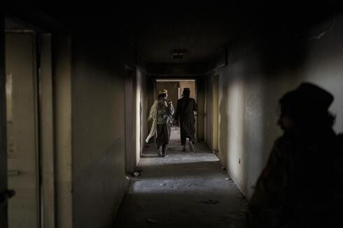 Combatientes talibanes caminan por los callejones de un área vacía en la prisión Pul-e-Charkhi.