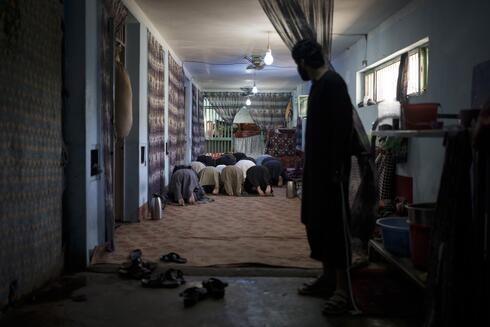Presos recientemente arrestados rezan dentro de la prisión de Pul-e-Charkhi en Kabul, Afganistán.