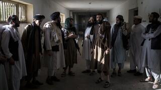 Combatientes talibanes, algunos ex presos, conversan en un área vacía de la prisión.
