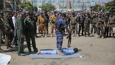 Un hombre en el piso, junto a su verdugo. Fue condenado por estar involucrado en el asesinato de un alto funcionario hutí: Ocurrió el sábado 18 de septiembre, en la plaza Tahrir en Sanaa, Yemen.