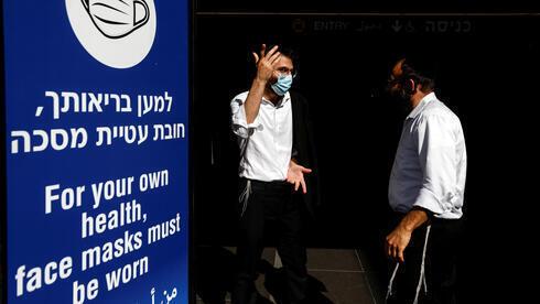 Dos hombres frente a un aviso para extermar cuidados ante el coronavirus, en el aeropuerto internacional Ben Gurión, de Tel Aviv.
