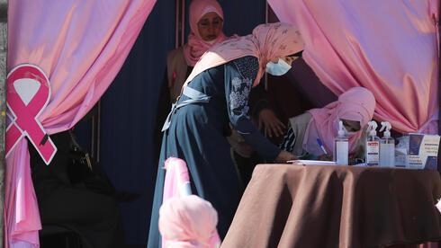 Una mujer palestina se registra para un chequeo voluntario de cáncer de mama, como parte de la campaña de concientización pública.