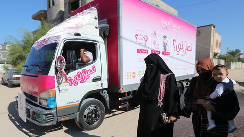 Mujeres palestinas pasan junto a una clínica móvil de control del cáncer de mama.